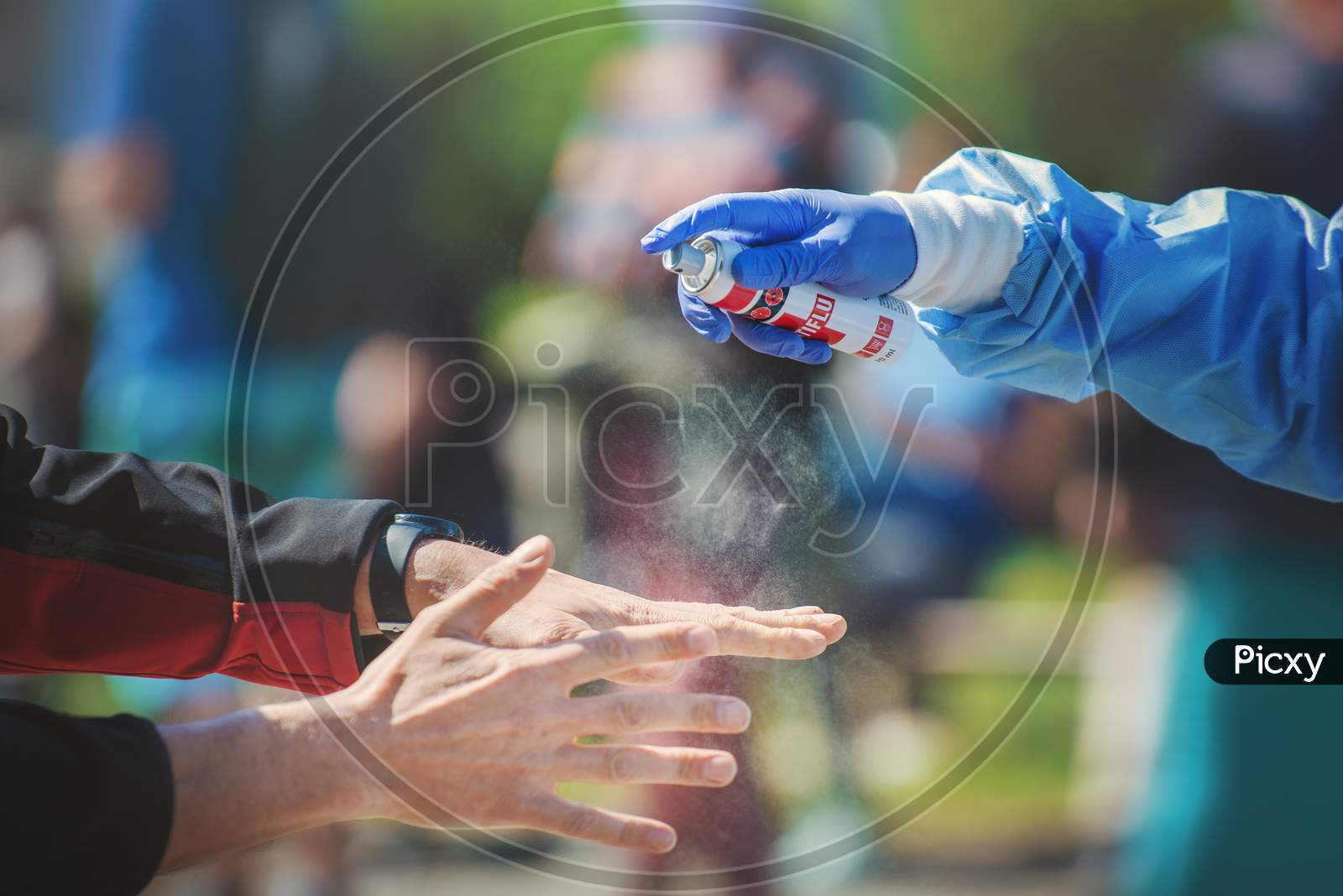 Close-up of a medic hand spraying disinfectant on a man's hands on the street.