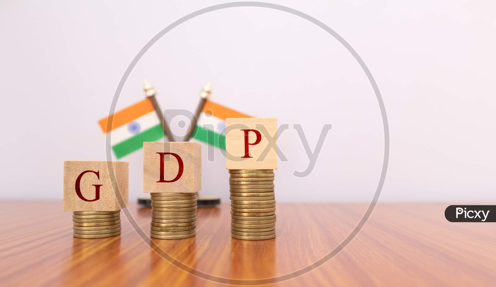 Gdp Or Gross Domestic Product In Wooden Block Letters On Coins In Increasing Order With Indian Flag As A Background.