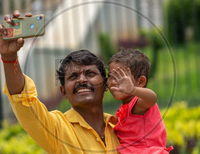 Bangalore, Karnataka India-June 04 2019 : Father And Little Cute Daughter Taking Picture Or Selfie With Mobile Phone Or Cellphone Camera At Tourist Places