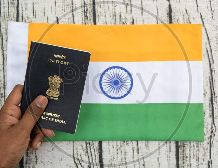 Person Holding Indian Passport With Hand On A Indian Flag As Background.