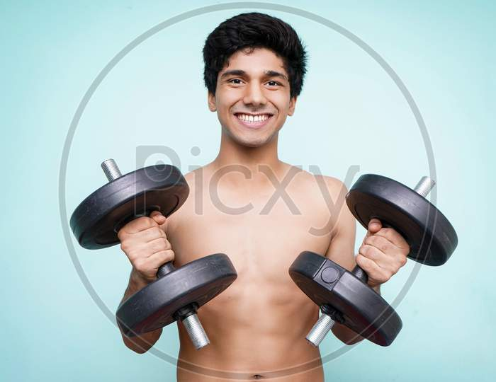 Young Handsome Asian Boy Holding Dumbbells On Both The Hands Looking Into The Camera While Smiling. Standing In Front Of A Blue Wall.
