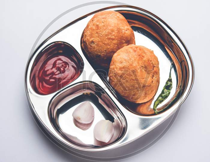 Kachori snack served in steel plate with tomato ketchup and onion