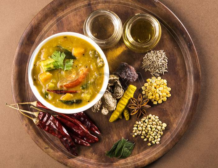 south indian vegetable sambar, in earthen bowl on white background