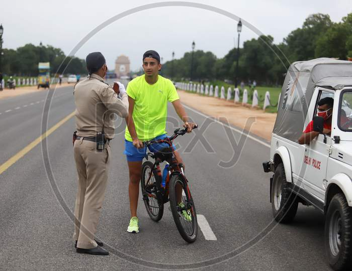 Delhi Police Official questions a cyclist for not wearing a mask near India Gate in New Delhi, India on July 07, 2020