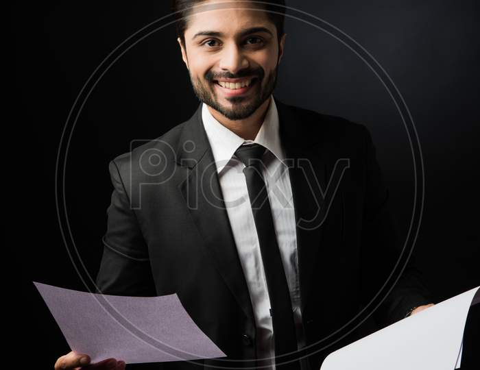 Indian Bearded Male businessman holding or reading documents or paper Roll while standing isolated over white background