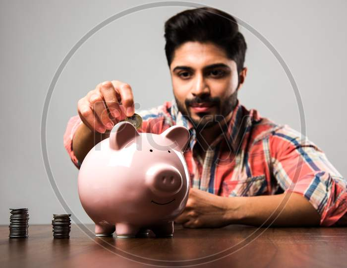 Indian Man with Piggy Bank, sitting at table
