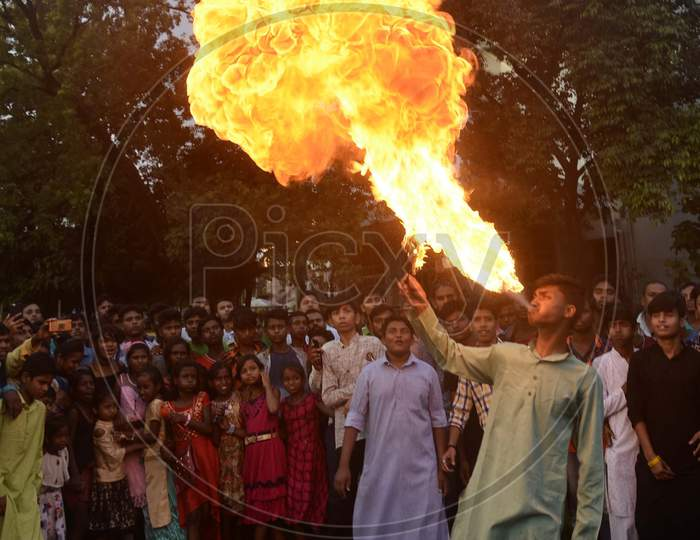 Fire eaters perform stunts on the occasion of Muharram during a procession