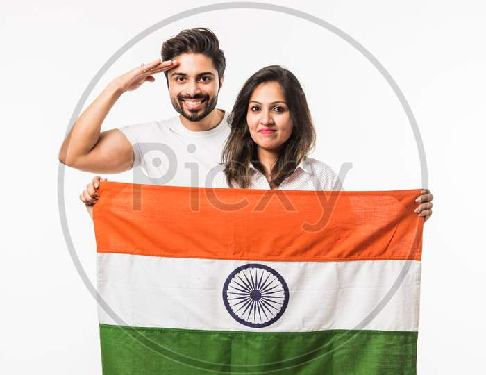 Young Couple holding Indian Flag on Independence or republic day, standing isolated over white background. selective focus