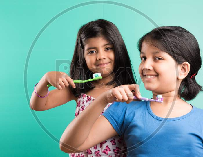 Small girls brushing teeth together