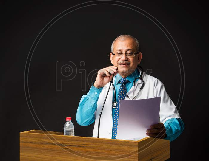 Senior Indian/asian male doctor speaking or giving lecture in mic. standing at podium and pointing something