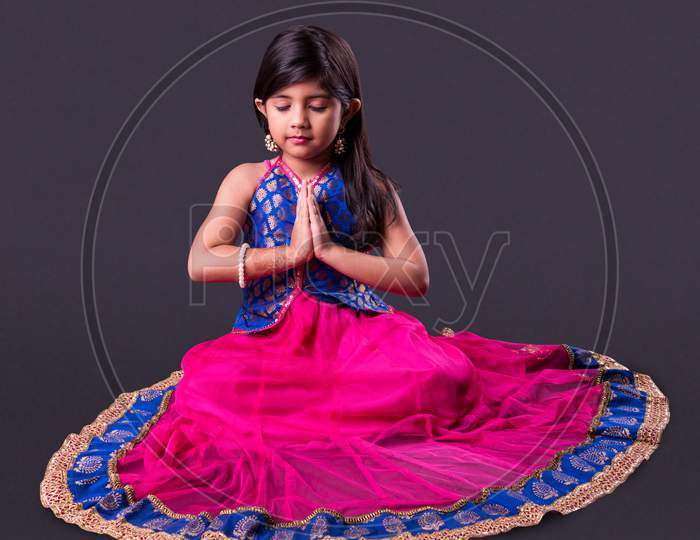 Small girl in namaskara or Prayer pose with both hands folded