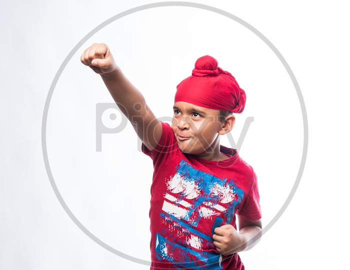 Portrait of Indian Sikh/punjabi little boy showing strength or Karate move while standing isolated over white background