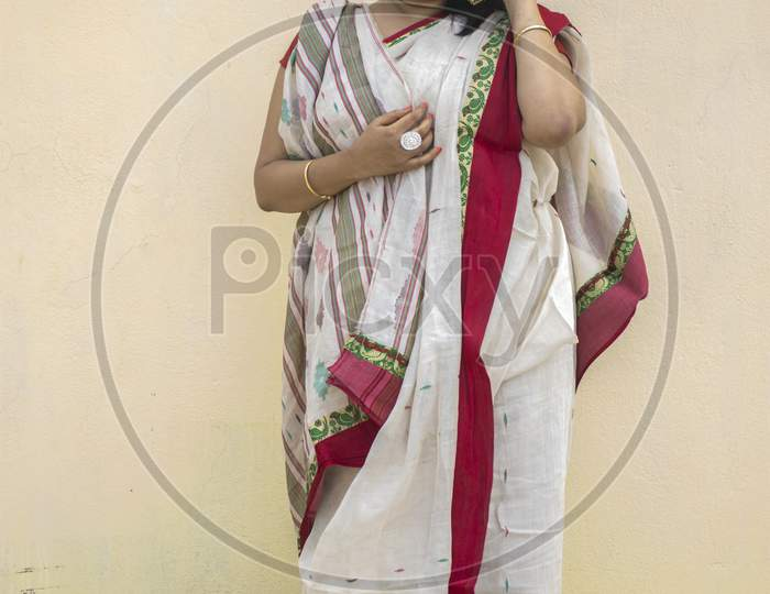 Beautiful Indian Female Model In Traditional Bengali Saree Looking Straight Happily With Slight Smiling Face In Yellow Background With Copy Space For Text