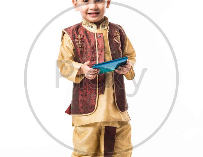 Portrait of Cute little Indian boy in traditional wear using smartphone / mobile playing games or watching videos, isolated over