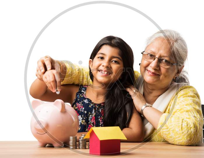 Small Girl inserting Rupee in piggybank with grand mother