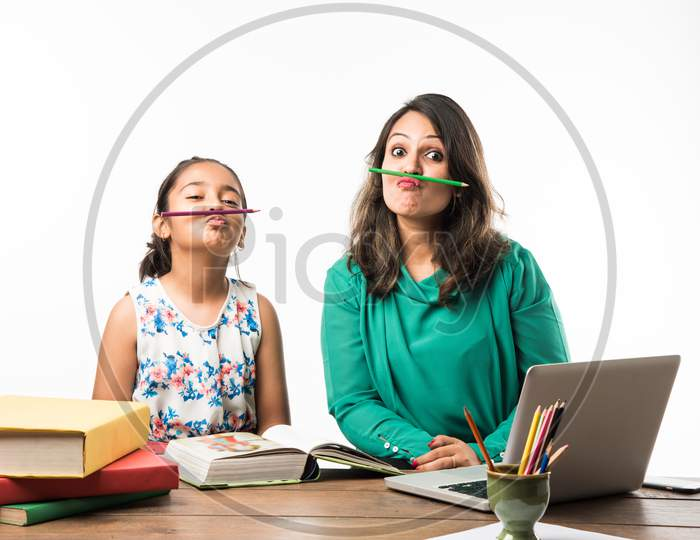 Indian girl studying with mother at study table with laptop and books