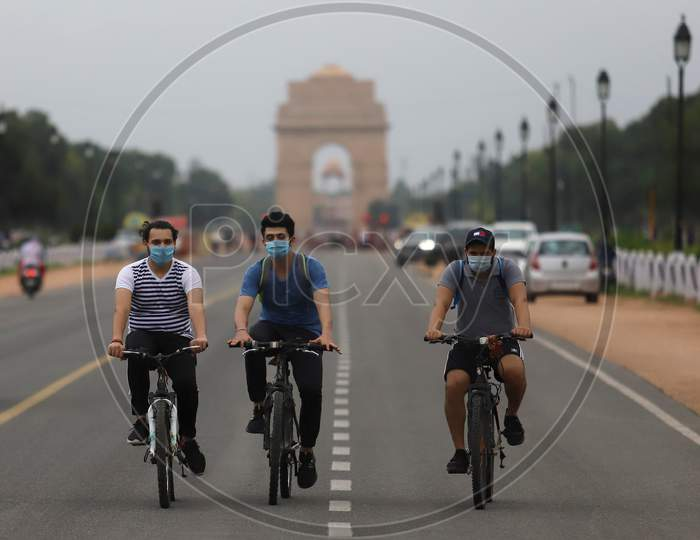 Three men ride their bicycles on Rajpath marg in New Delhi on July 07, 2020