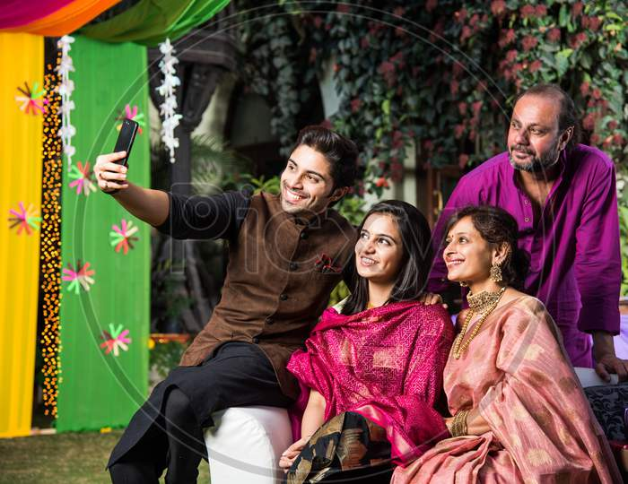 Indian family taking selfie picture using smartphone