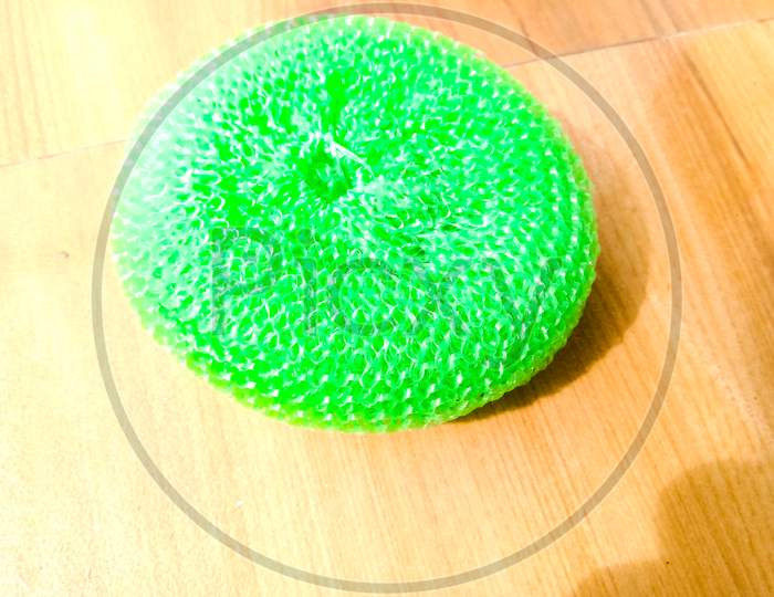 A Green Plastic Scrubber Placed On The Floor.