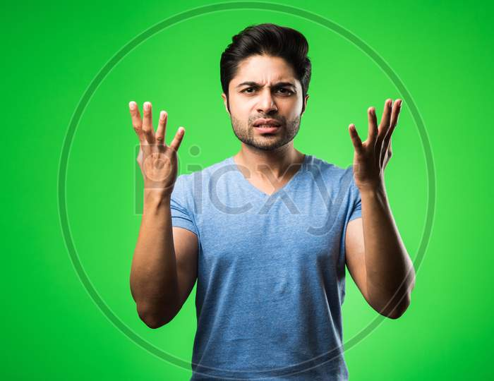 Handsome Indian / asian depressed man standing isolated over green background looking stressed and nervous having  Anxiety probl