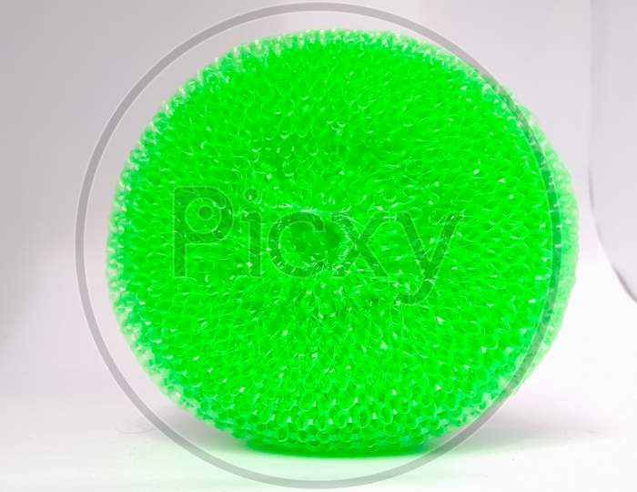 A Closeup Shot Of A Green Plastic Scrubber Placed Isolated Vertically On A White Background.