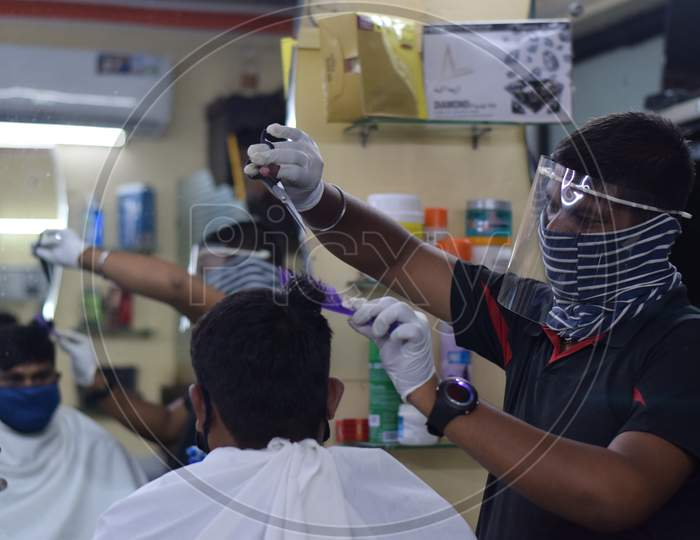 Hyderabad, Telangana, India. july-14-2020: A hairdresser, wearing a protective face mask, works in a barber shop. Reopen after Lockdown for covid-19.