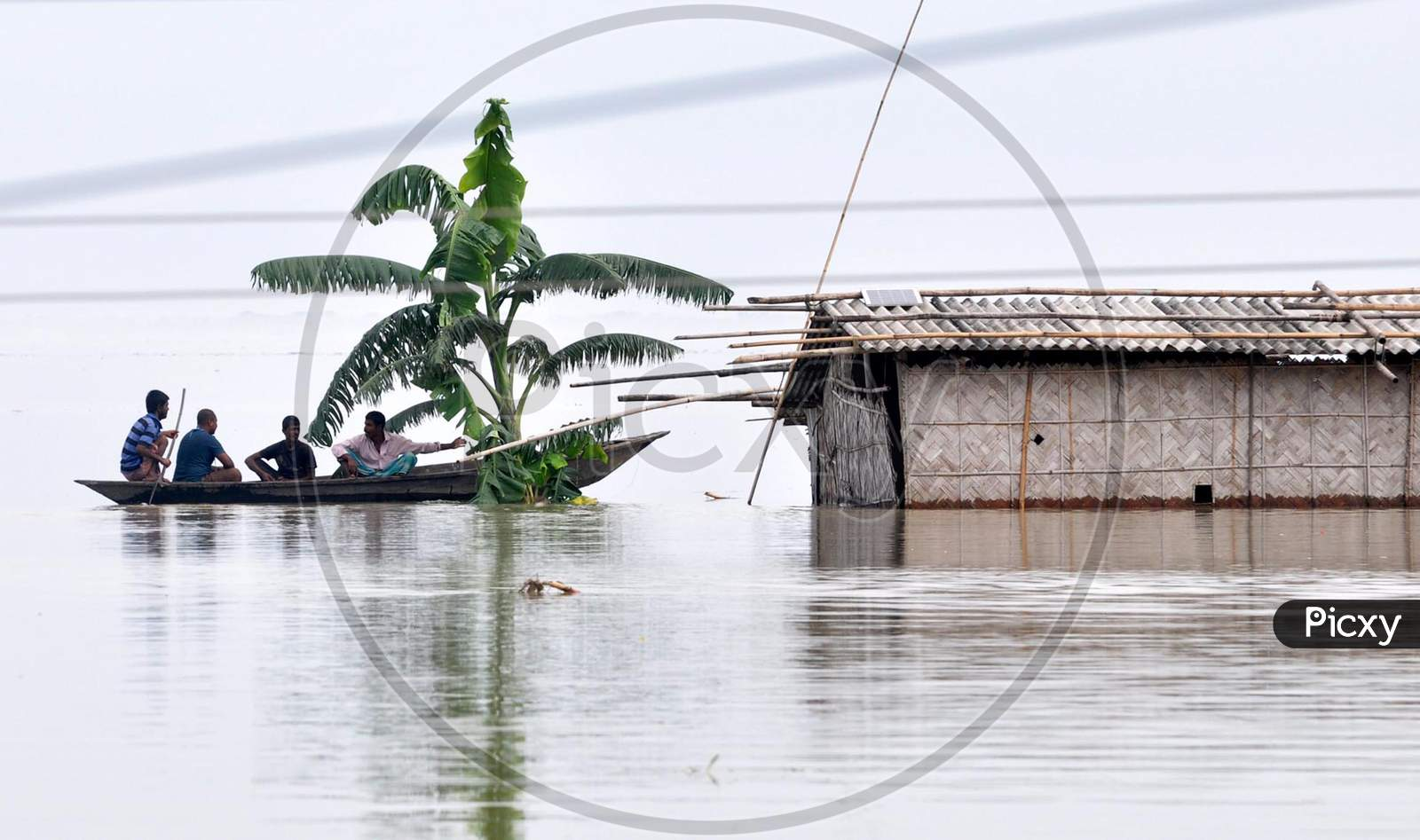 People navigate the flood-affected areas using a boat in Hatisela in Kamrup district of Assam on July 14, 2020