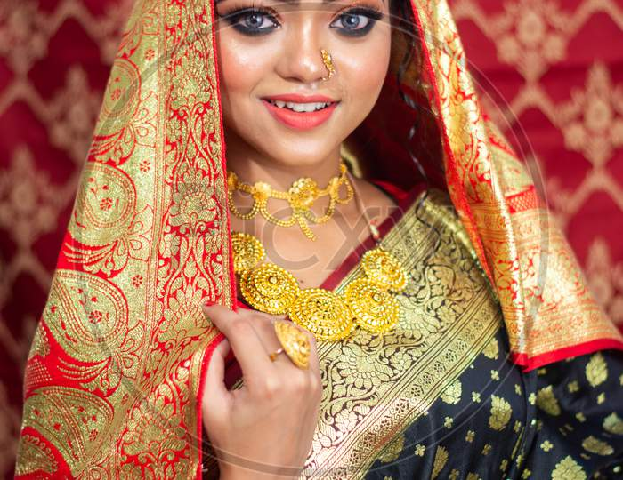 Portrait Of A Beautiful Elegant Female Model In Traditional Ethnic Indian Asian Bridal Costume With Makeup And Heavy Jewellery, Looking At Camera