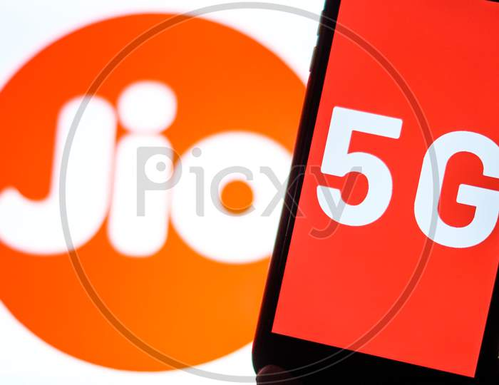 Close Up shot of a Mobilephone or Smartphone with 5G on Screen and Jio Logo in the Background - A Concept of Jio 5G