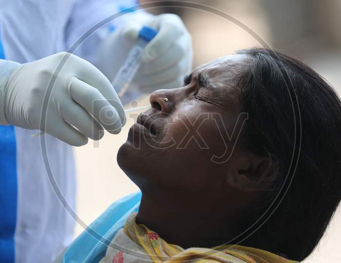 A health worker collects a swab sample from a woman for Covid-19 testing in Maratha Basti, Jammu on July 16, 2020