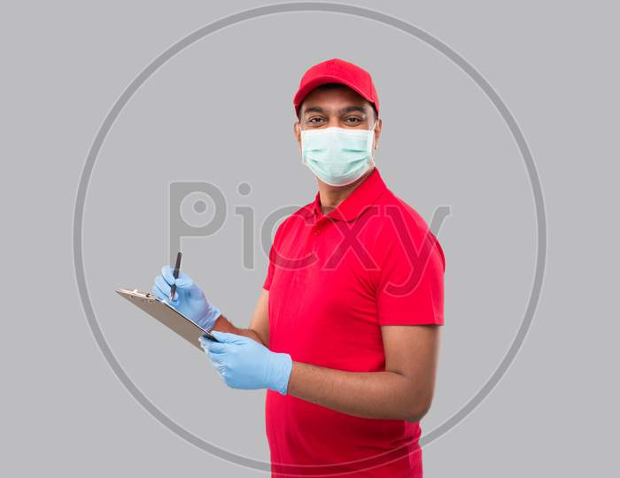 Delivery Man Writing In Clipboard Wearing Medical Mask And Gloves Watching In Camera. Indian Delivery Boy Clipboard