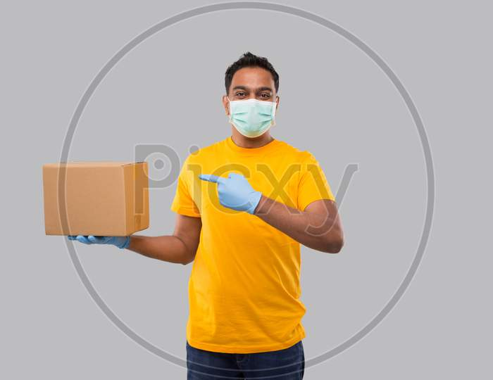 Indian Man Pointing At Box Wearing Medical Mask And Gloves Isolated. Yellow Tshirt Delivery Boy. Home Delivery. Quarantine Hero.