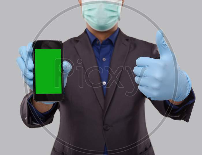 Businessman Showing Phone And Thumb Up Wearing Medical Mask And Gloves. Indian Business Man Technology Business At Home. Phone Green Screen Isolated