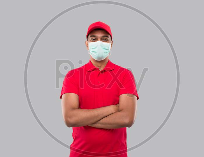 Delivery Man Standing Hands Crossed Wearing Medical Mask Isolated. Indian Delivery Boy In Red Uniform