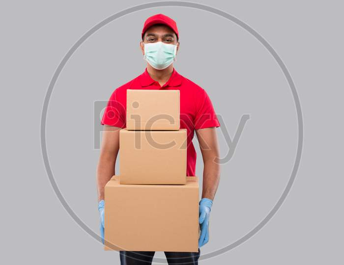 Delivery Man Holding Carton Boxes Wearing Medical Mask And Gloves Isolated. Indian Delivery Boy Smiling With Boxes In Hands