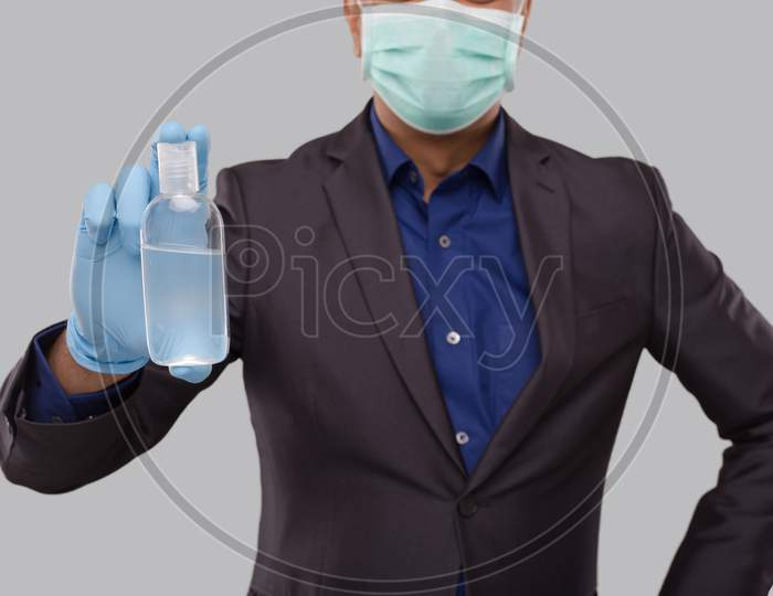 Businessman Showing Hands Sanitizer Wearing Medical Mask And Gloves Close Up. Indian Business Man Holding Hand Antiseptic