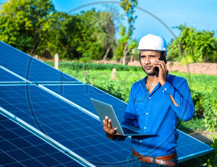 Young Male Engineer Talking On Phone With Laptop In Hand Standing Near Solar Panels, Agriculture Farm Land With Clear Blue Sky Background, Renewable Energy, Clean Energy.