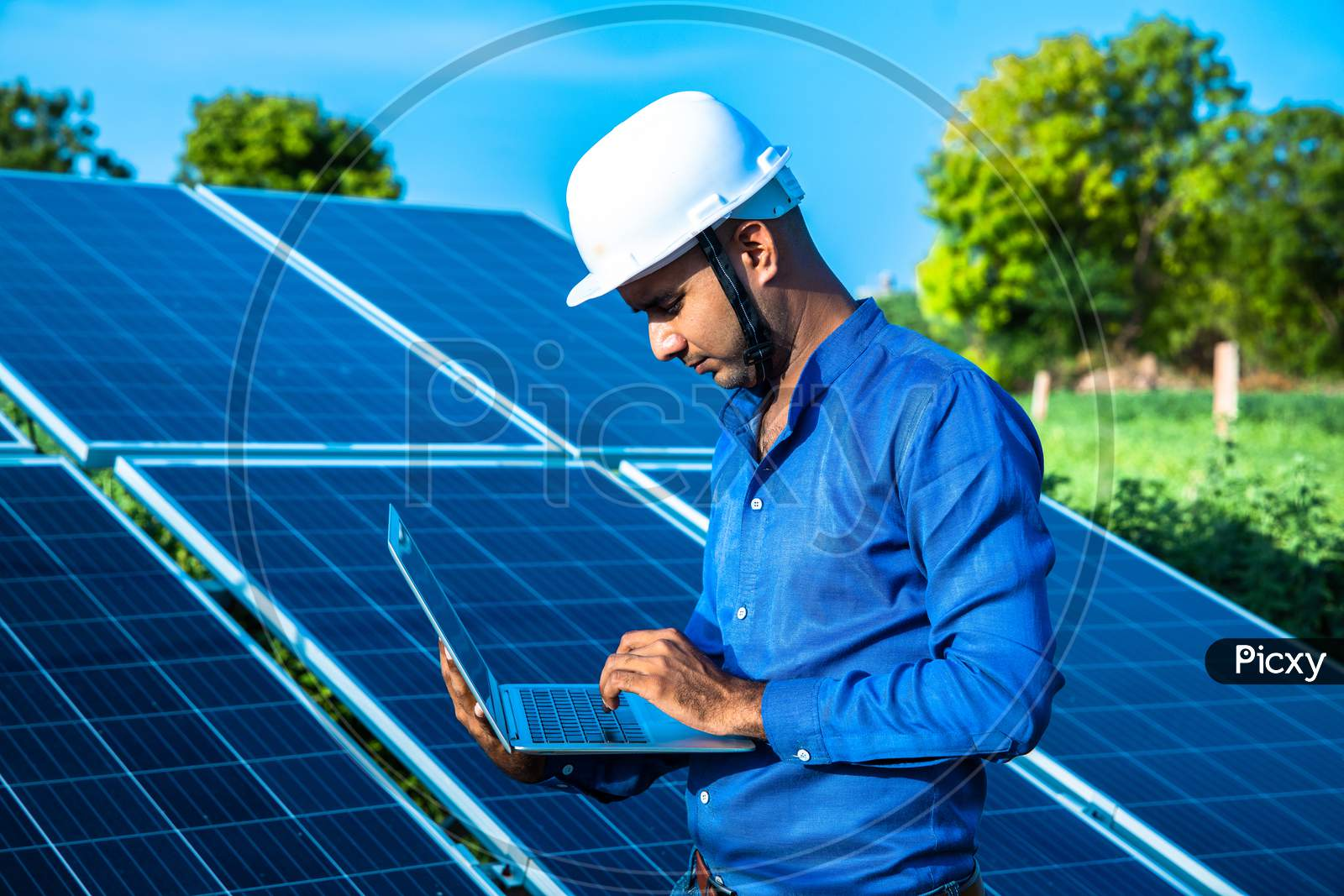 Young Male Engineer With Laptop In Hand Standing Near Solar Panels, Agriculture Farm Land With Clear Blue Sky Background, Renewable Energy, Clean Energy.