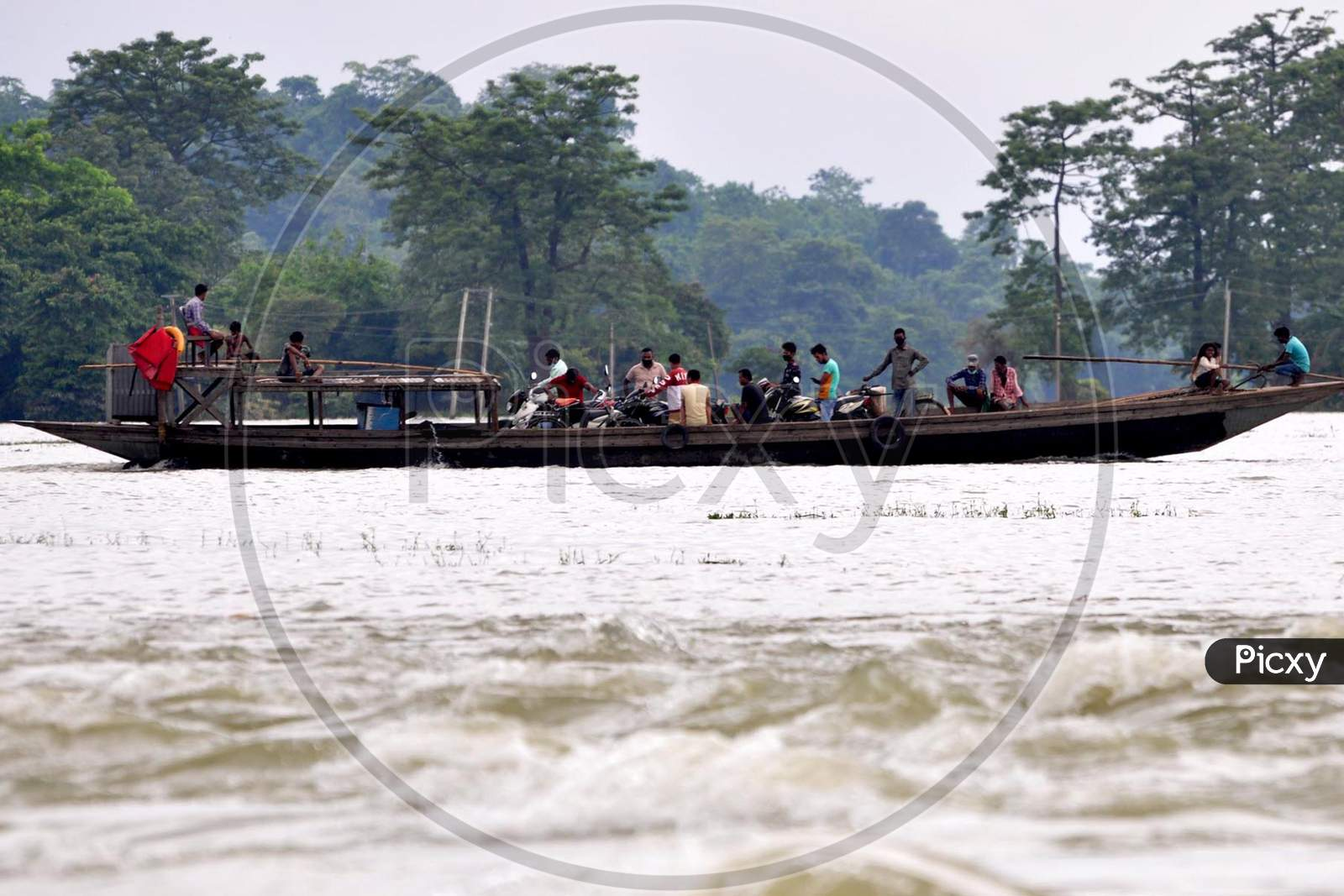 Villagers cross a flooded area on a boat at Mayong village in Morigaon, Assam on July 18, 2020