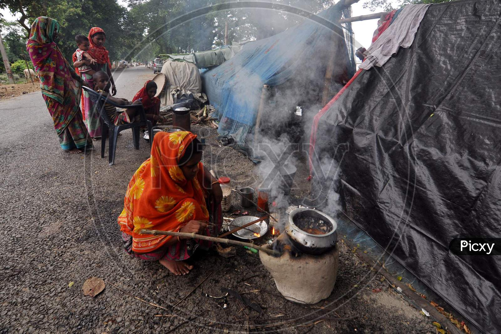 A women cooks food at a makeshift relief camps on the road at Sildubi in Morigaon, Assam on July 18, 2020