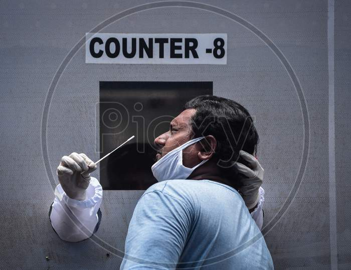 A medic collects a swab sample of a man for the COVID-19 test from a mobile swab collection vehicle in Vijayawada.
