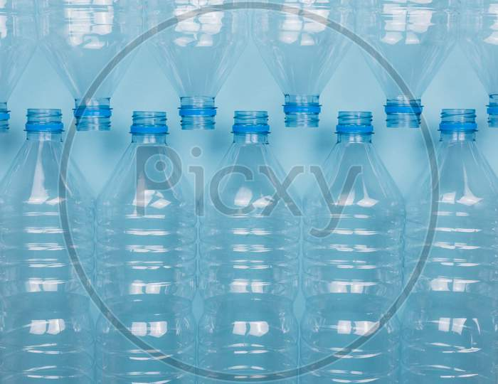 Empty Clear Plastic Bottles Without Caps Stacked On A Blue Background. Recycling And Environment Concept.