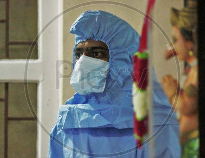 A Healthcare worker wearing a Personal Protective Equipment (PPE) waits to screen people at a camp set up for the coronavirus disease (COVID-19),inside a temple in  Mumbai, India on July 15, 2020.