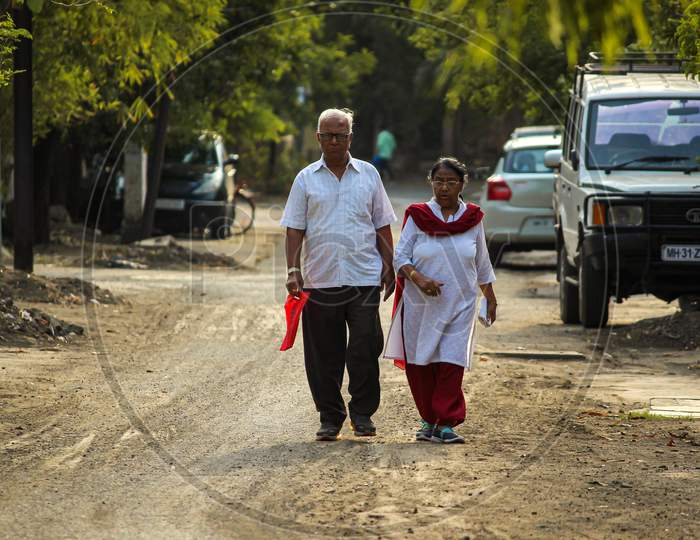Old Couple Talking A Walk Down The Street