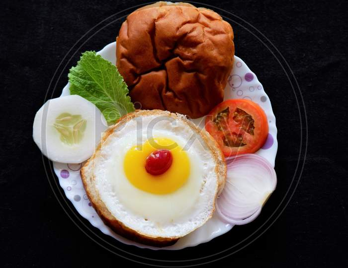 Homemade burger bun with fried egg and fresh vegetables on a white plate . Top view image.