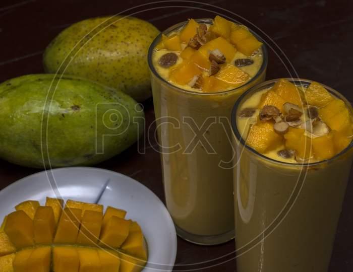 Mango Lassi Decorated With Mango Pulp Raisin Almonds And Ripe Mango In Background Mango Slice In Foreground