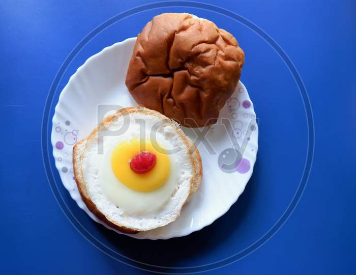 Homemade burger bun with fried egg on a white plate . Top view image.