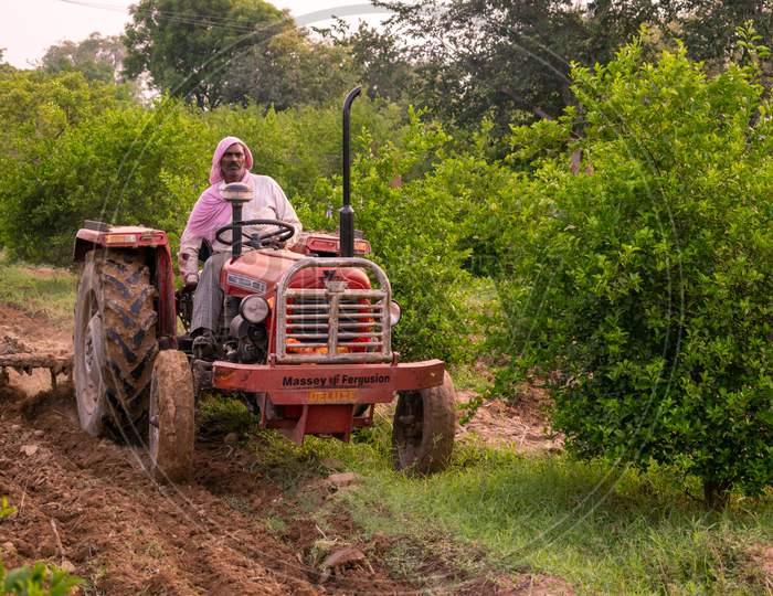 Farmers ploughing their fields using tractor to prepare it for growing kharif crops during monsoon or rainy season in Rajasthan