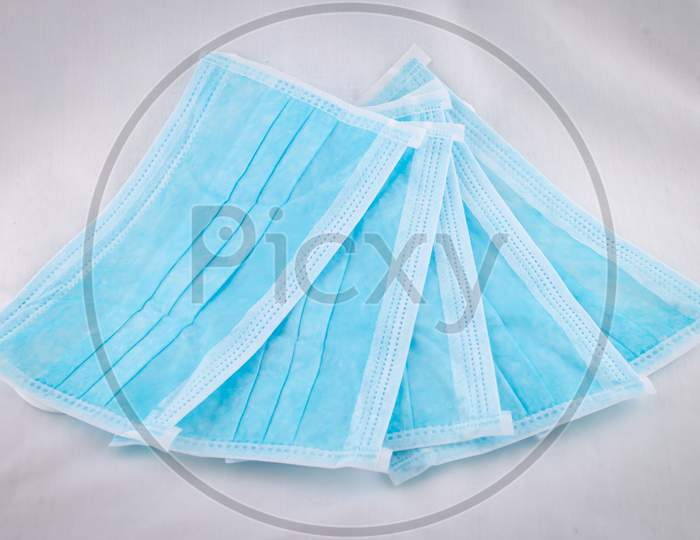 Five surgical face masks on white