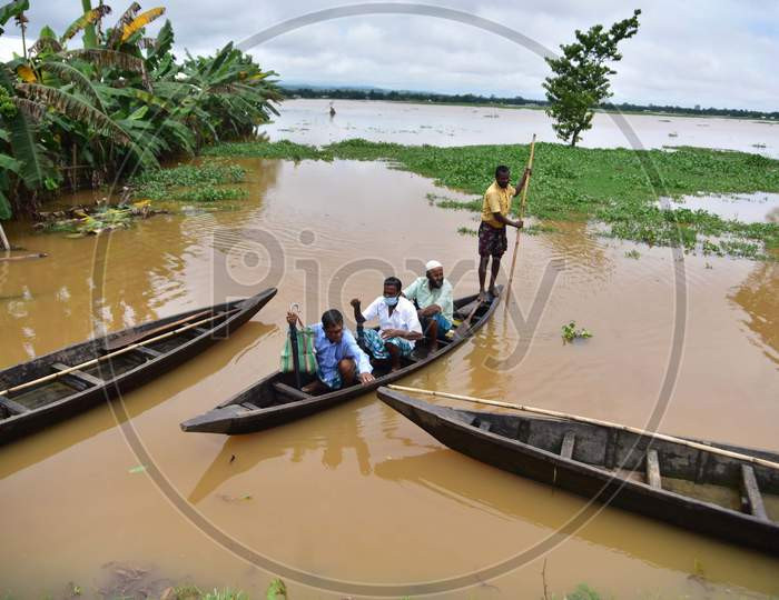 Villagers use a boat to reach to a safer place in a flood-affected village in Nagaon, Assam on July 22, 2020